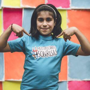 niña usando camiseta azul multiplicando sonrisas